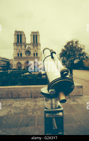 Binoculars pointed at Notre Dame Cathedral Paris France. The photo has been toned with a retro style - Stock Image