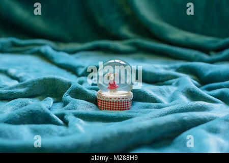 Vast area covered with beautiful cyan blanket drapes, and a crystal snowglobe with a mouse in it, in the center - Stock Image