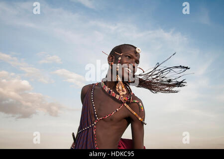 Happy Maasai Warrior Portrait with Braids Flying Against the Sky - Stock Image