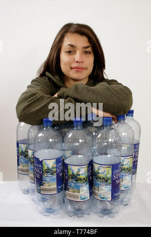 teenage girl in fleece jacket standing with 12 large plastic water bottles to illustrate the reconstitution of plastic bottles into synthetic fleece - Stock Image