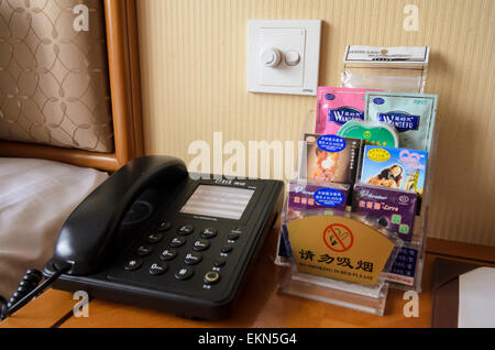 Bedside table of a Chinese hotel - telephone, condoms and lube oil - extra paid-for services, China - Stock Image