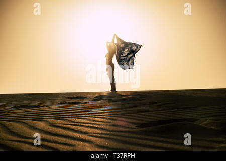 Happiness and freedom concept with woman standing on the sand dunes at the desert beach and play with the wind feeling the nature and independence - p - Stock Image