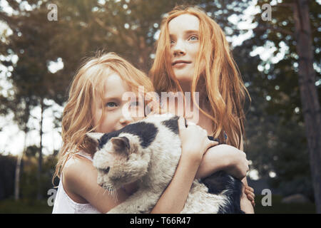 Sisters holding cat - Stock Image