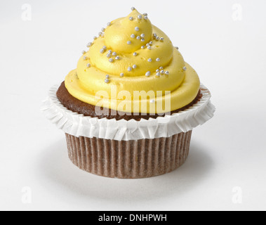 A single decorated yellow cupcake on a white background. - Stock Image