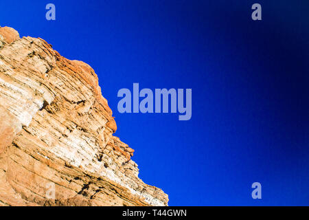 Red and orange formations of stone make a cliff with blue sky in the desert. - Stock Image