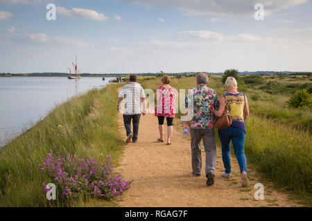 Walkers head off along the estuary path by the River Blackwater, near Maldon, Essex - Stock Image