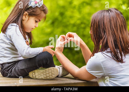 Young mom shows her little girl how to make heart shape on bench in forest.Happy mother and daughter moments with love and natural emotion - Stock Image
