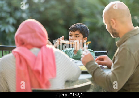 Family eating dinner at patio table - Stock Image