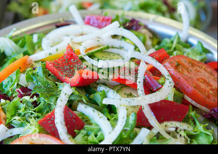 Fresh and healthy mixed salad with lettuce, red peppers, tomatoes and onions, as a starter, side dish or first course for a vegetarian or vegan diet - Stock Image