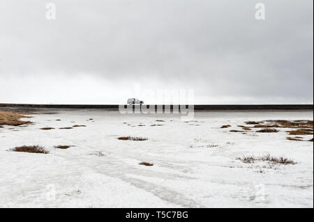 Car driving on a road beside a frozen lake in Iceland - Stock Image