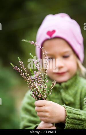 Girl holding heather - Stock Image