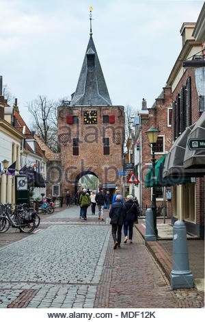 People stroll through the Vischpoort, a defensive tower built in the early 15th century; the passageway added in 1592 leads to the Elburg harbor. - Stock Image