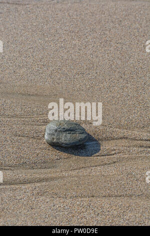 Small stone sitting alone on wet beach sand bed. Metaphor: Last Man Standing, odd man out, odd one out, rock all alone, single stone, hidden from view - Stock Image