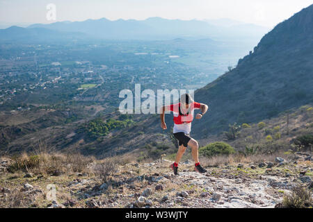 A strong, male trail runner climbs up the rocky trail towards the arid mountains surrounding the town of El Arenal, Hidalgo, Mexico. - Stock Image