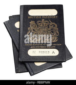 A pile of three old style blue passports for United Kingdom of Great Britain and Northern Ireland - Stock Image