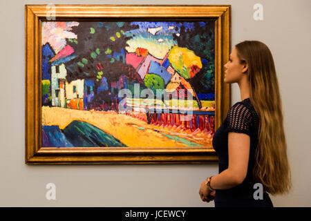 London, UK. 15 June 2017. A Sotheby's employee looks at the painting Murnau - Landschaft mit grünem Haus - Stock Image