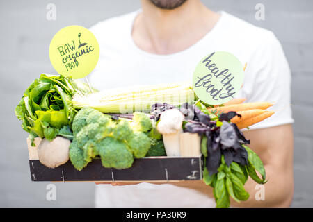 Holding box full of fresh vegetables from the local market - Stock Image