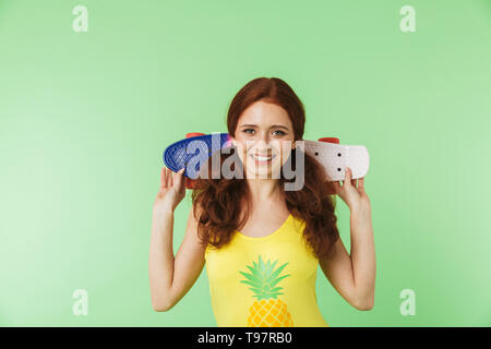 Image of a beautiful happy young redhead girl posing isolated over green wall background with skateboard. - Stock Image