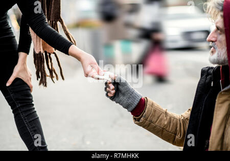 A midsection view of woman giving money to homeless beggar man sitting in city. - Stock Image