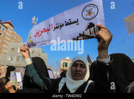 A Palestinian woman holds a banner saying, 'down with the Bahrain conference' during a protest against Bahrain's workshop for U.S. peace plan, in southern Gaza Strip. - Stock Image