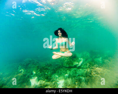 young female teenager swimming underwater - Stock Image