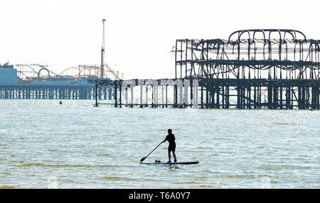 Brighton UK 30th April 2019 - A paddle boarder enjoys the warm sunny weather off Hove beach near the West Pier this morning with it forecast to reach into the high teens in some parts of the South East today. Credit: Simon Dack/Alamy Live News - Stock Image