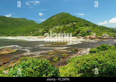 view of a beach and sky with mountains in the background in Florianopolis, Brazil - Stock Image