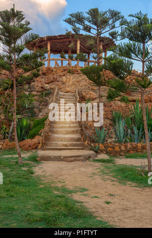 Natural stone stairway with green bushes on both sides leading to wooden pergola with partly cloudy sky at public Park in summer time - Stock Image