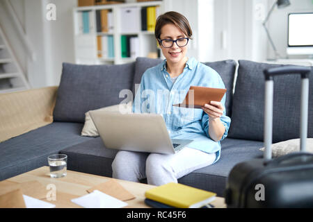 Young contemporary woman with laptop and passport ordering tickets online while looking forwards for vacation - Stock Image