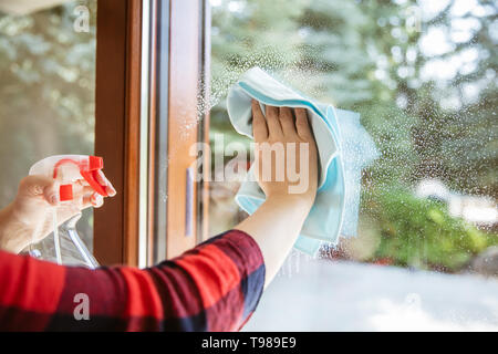 Woman is wiping the cleaning liquid from the window with garden in the background. - Stock Image