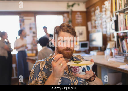 Creative businessman eating soup in office - Stock Image
