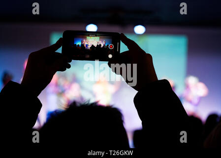 A smart phone held in the air to photograph a childrens school show - Stock Image