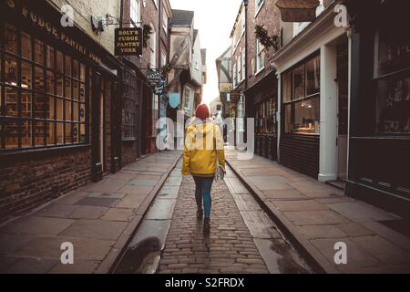 A rear view of a fashionable young girl walking along a historic mediaeval street known as the shambles in the historic city of York UK - Stock Image