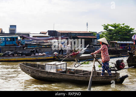Woman selling bread loaves from a small traditional boat in the floating market on Hau River. Can Tho, Mekong Delta, Vietnam, Asia - Stock Image