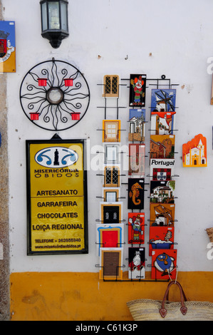 Postcard rack and chocolate shop sign in the medieval town of Obidos some 50 miles north of Lisbon, Portugal - Stock Image