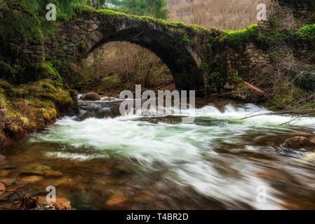 Old stone bridge over mountain river - Stock Image