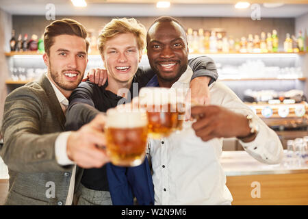 Three friends drink beer together and celebrate in a bar or pub - Stock Image