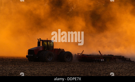 Tractor plowing field at sunset - Stock Image
