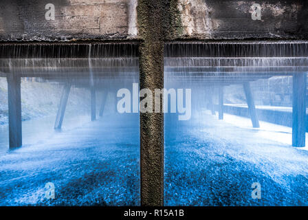 Falling water from industrial cooling tank making an abstract image. - Stock Image