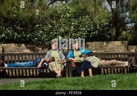 Southwold Suffolk England. 1980's Men and women asleep on a bench enjoying the sunshine. - Stock Image