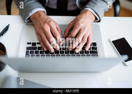 A midsection of businessman with laptop sitting at the desk, working. A top view. - Stock Image