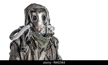 Scary post apocalyptic survivor wearing full-face gas mask under tattered hood. - Stock Image