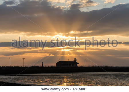 Morecambe, Lancashire, UK, 9 April 2019. UK Weather: A beautiful sunset over the Stone Jetty and Morecambe Bay as the clouds split the sunlight into distinct rays fanning out above the old station building. The spectacular sunsets at Morecambe and the view of the Lake District Hills across the bay continue to attract tourists throughout the year. Credit: Keith Douglas News/Alamy Live News - Stock Image