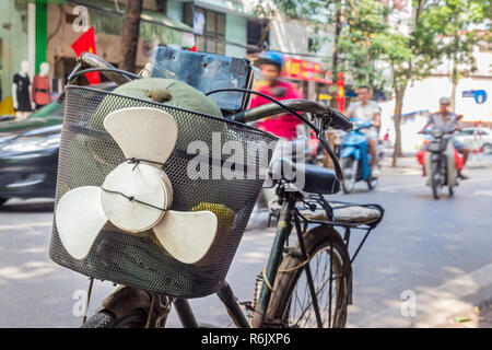 bicycle with funny, amusing plastic propeller on the basket on the street of Hanoi in Vietnam, blurred background, street and scooters. - Stock Image