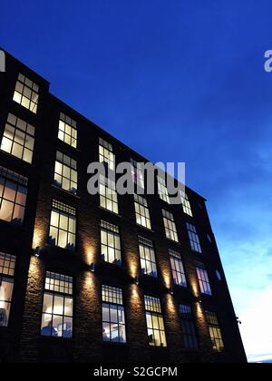 The exterior of a modern office block at night with the glow of window light in the rows of windows lighting up the interior rooms - Stock Image