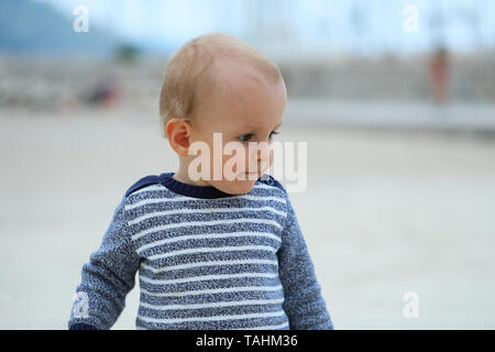 Cute Blond Baby Boy Wearing A Sweater On The Sandy Beach, Close Up Portrait - Stock Image