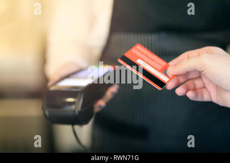 Cropped shot of an unrecognizable man paying for his purchase by contactless card. Soft focus on card - Stock Image