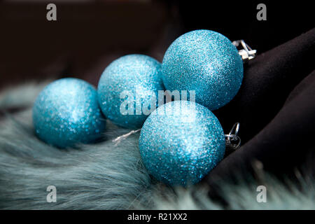 Sparkly blue holiday ornaments on black and green furry background - Stock Image