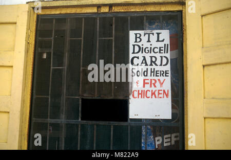 In a small town in Belize a mobile phone shop supplements sales by also selling 'fry chicken.' - Stock Image