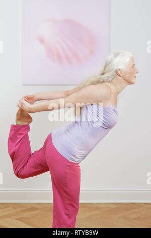 Senior woman with lang gray hair doing yoga exercise at home in front of a shell picture, position dancer intro - Stock Image
